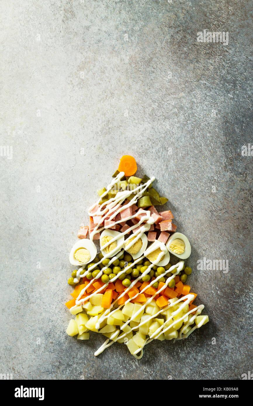 Weihnachtsbaum aus Salat Olivier auf grauem Schiefer, Stein oder Metall Hintergrund. schöne Weihnachten und Neujahr Stockfoto