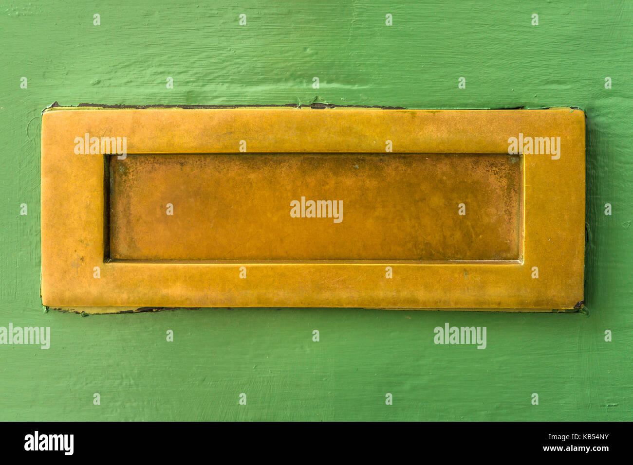 Eine gut verwendet nicht polierten Messing Briefkasten auf einem rund grün lackiert Haustür in Großbritannien. Stockbild
