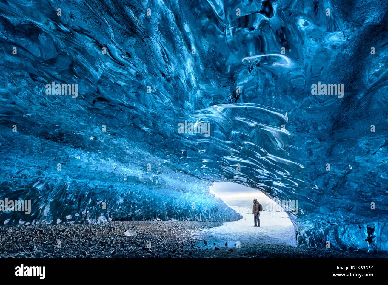 Ansicht von innen Eis Höhle unter dem Vatnajökull Gletscher mit Person für Skala, in der Nähe der Lagune Jokulsarlon, Stockfoto