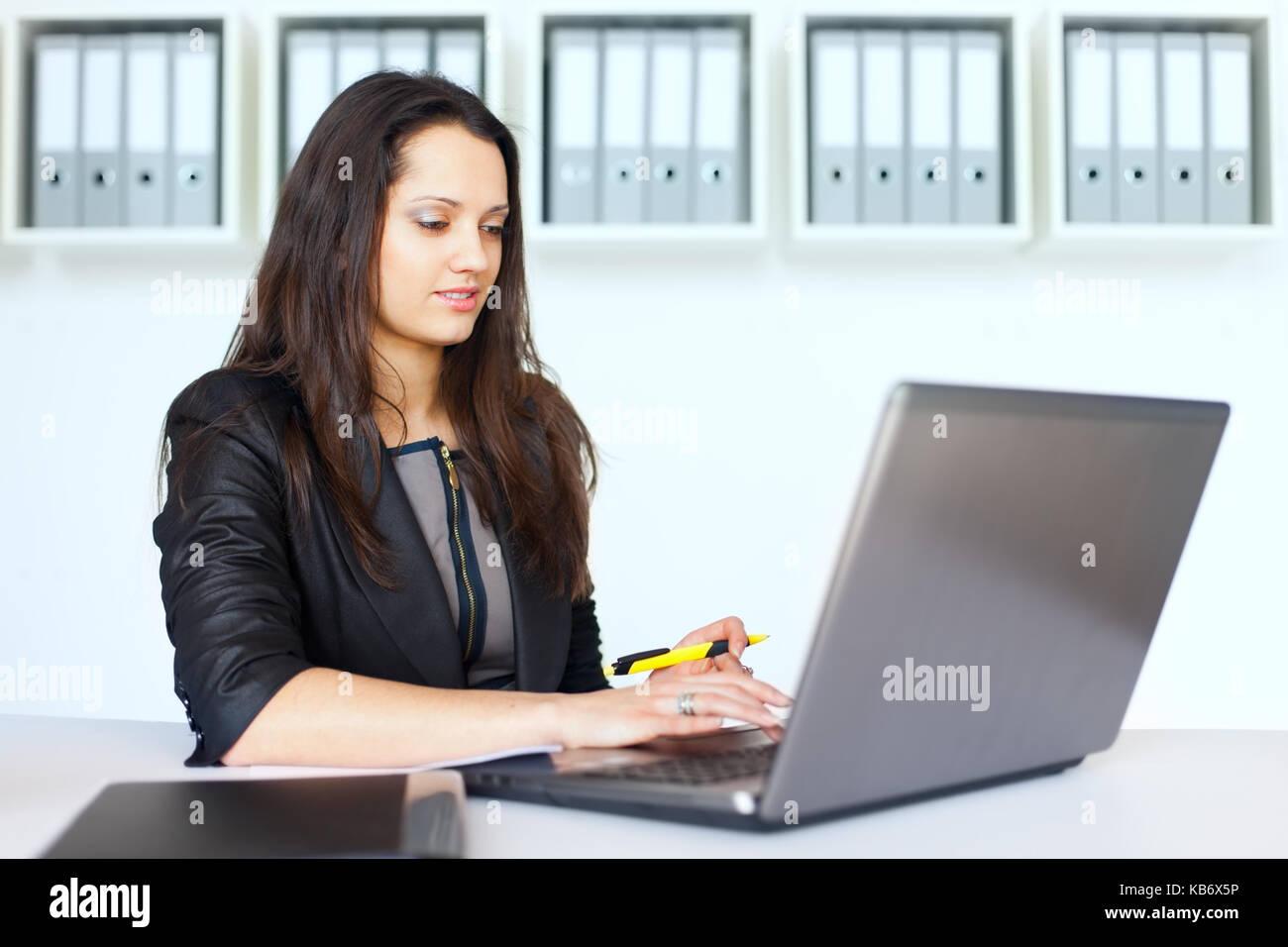 Porträt der schöne Junge brunette business Frau, die an einem Notebook arbeitet im Büro Stockbild