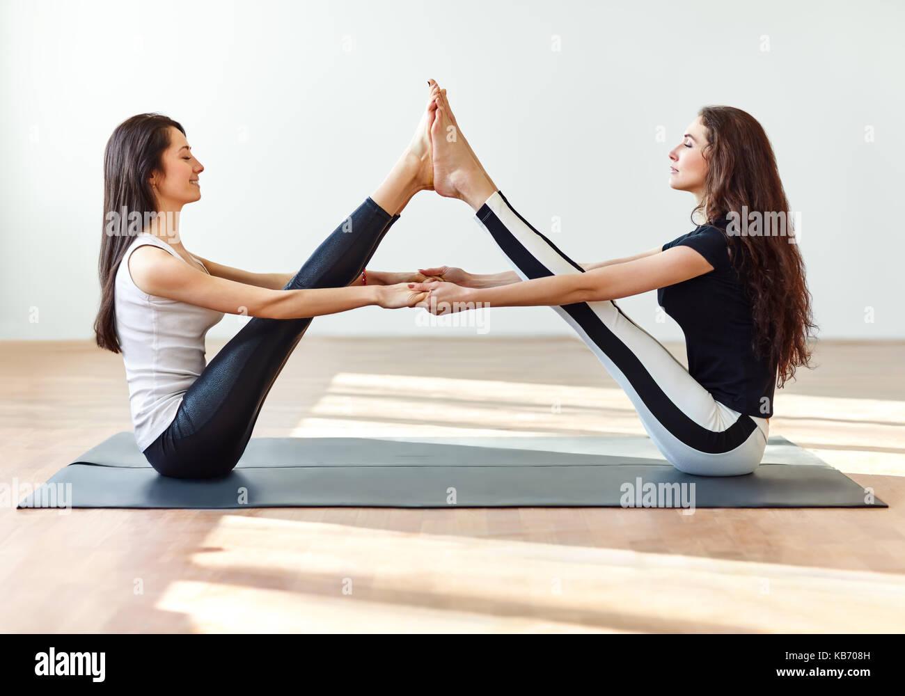 Zwei junge Frauen Yoga Asana buddy Boot dar. Paripurna Navasana ...