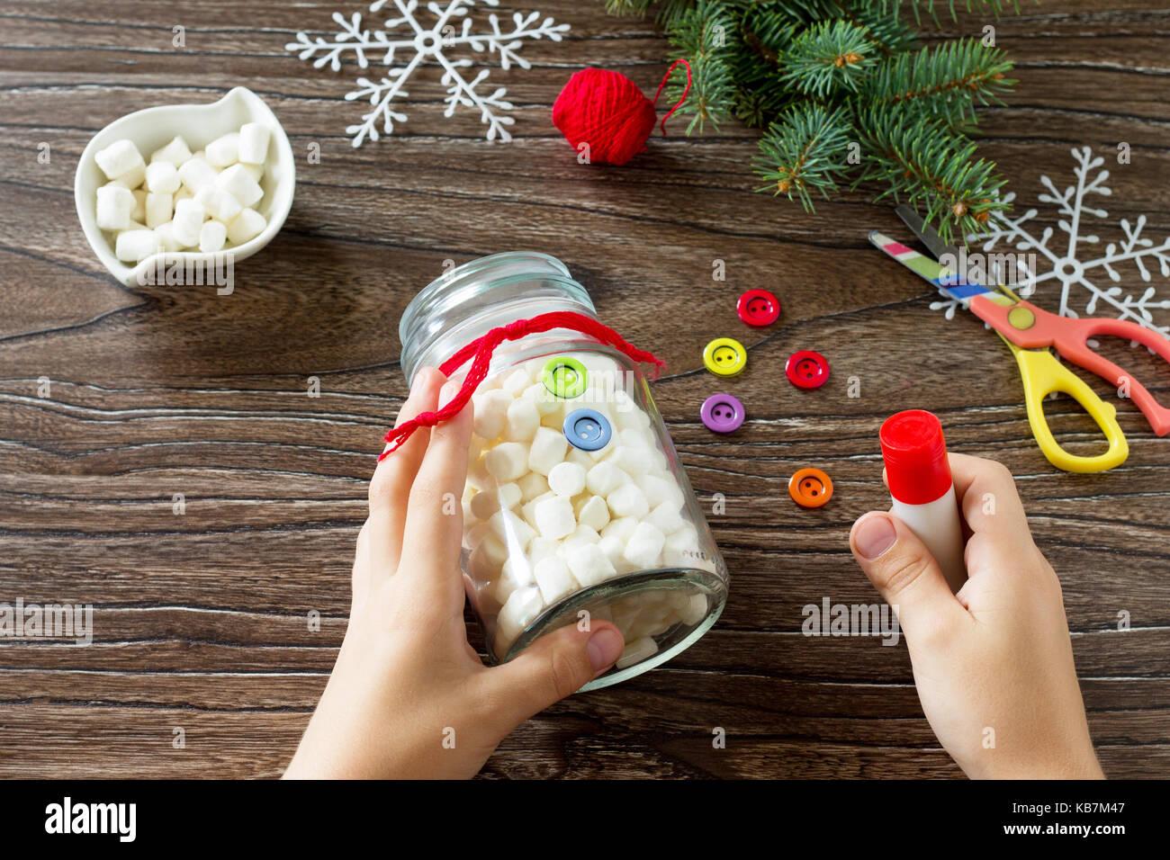 Ein Kind ist ein Weihnachten mit einem Schneemann von Süßigkeiten ...
