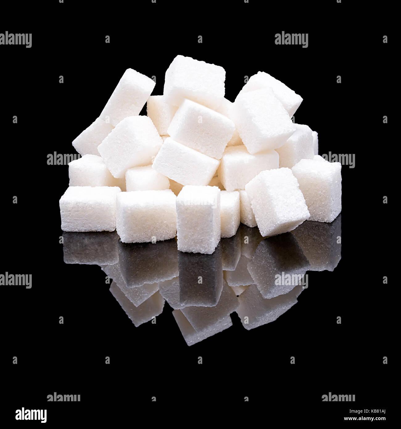 Würfel weißen Zucker aus Zuckerrüben mit einem echten Reflexion auf einem schwarz glänzenden Hintergrund Stockfoto