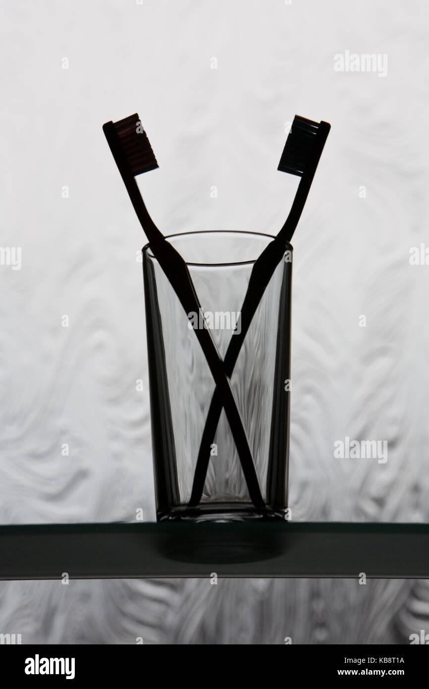 Zwei Zahnbürsten nach einander in einem Glas, gegen eine ...