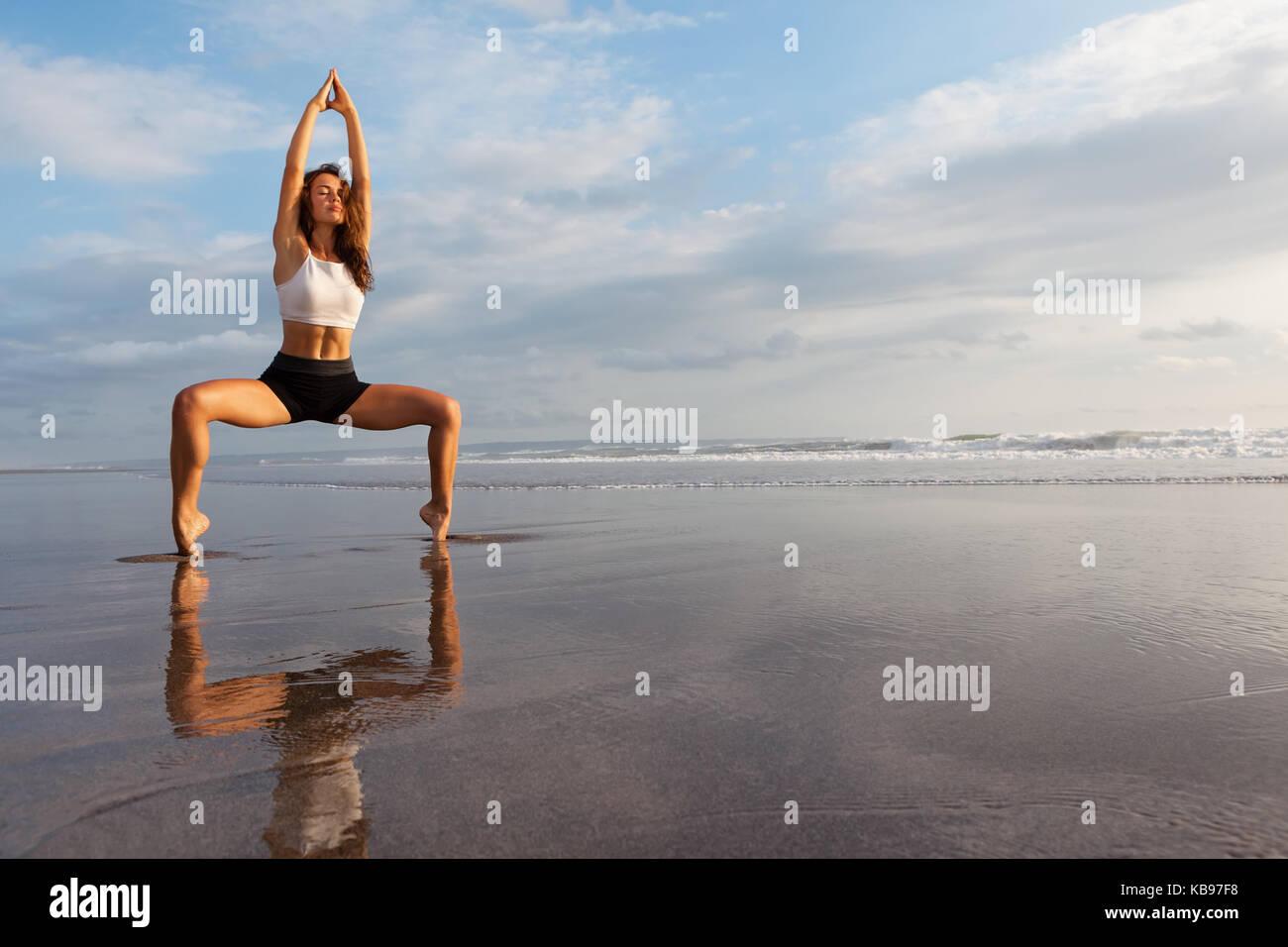 Meditation über Sonnenuntergang Himmel Hintergrund. Junge aktive Frau in Yoga Pose auf Meer Strand, Stretching Stockbild