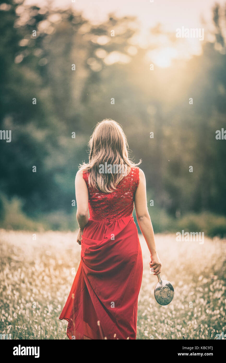 Mädchen gehen in einem Feld bei Sonnenuntergang, im roten Kleid, holdinh ein silberner Spiegel Stockbild