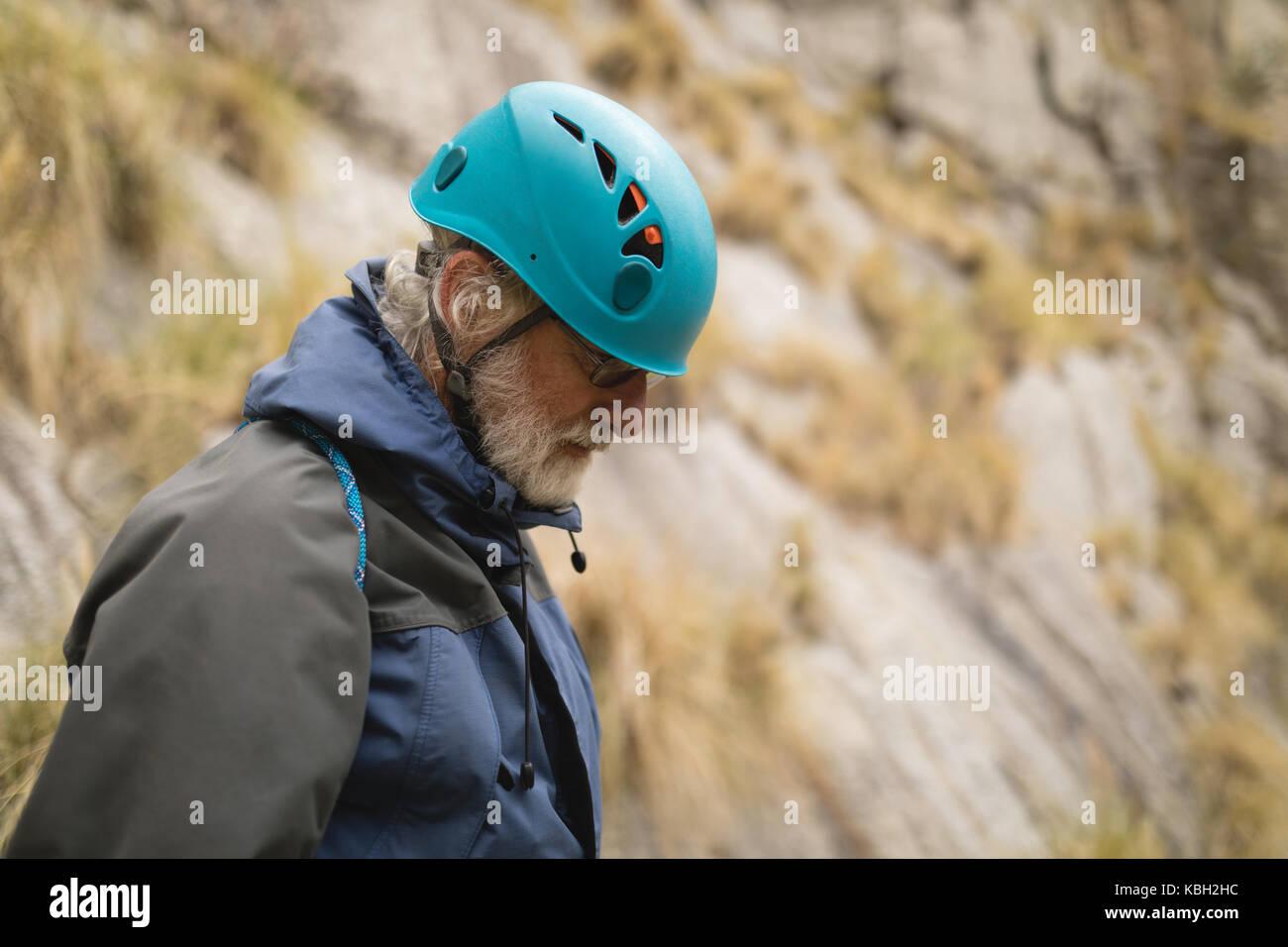 Älterer Mann durch das Tragen von schützender helm beim Bergsteigen Stockbild