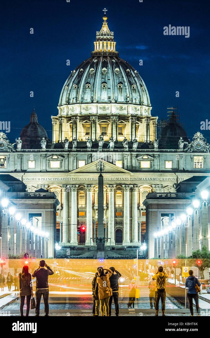 Blick auf den beleuchteten St. Peter Basilika, die Straße Via della Conciliazione und leichte Spuren von Autos Stockbild