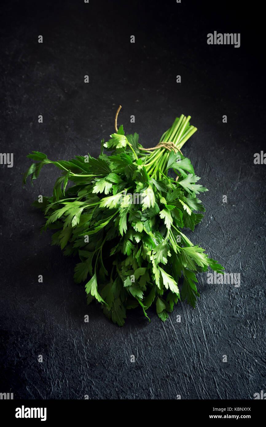 Organische italienische Petersilie closeup auf schwarzen Hintergrund, gesunde vegetarische Lebensmittelzutat. frische Stockbild