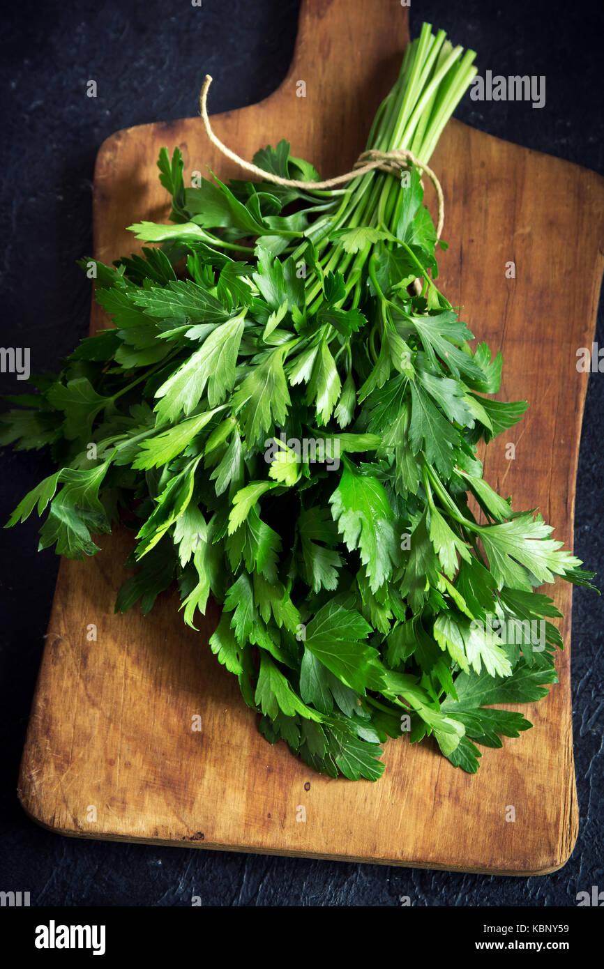 Organische italienische Petersilie closeup auf ein Schneidbrett, gesunde vegetarische Lebensmittelzutat. frische Stockbild
