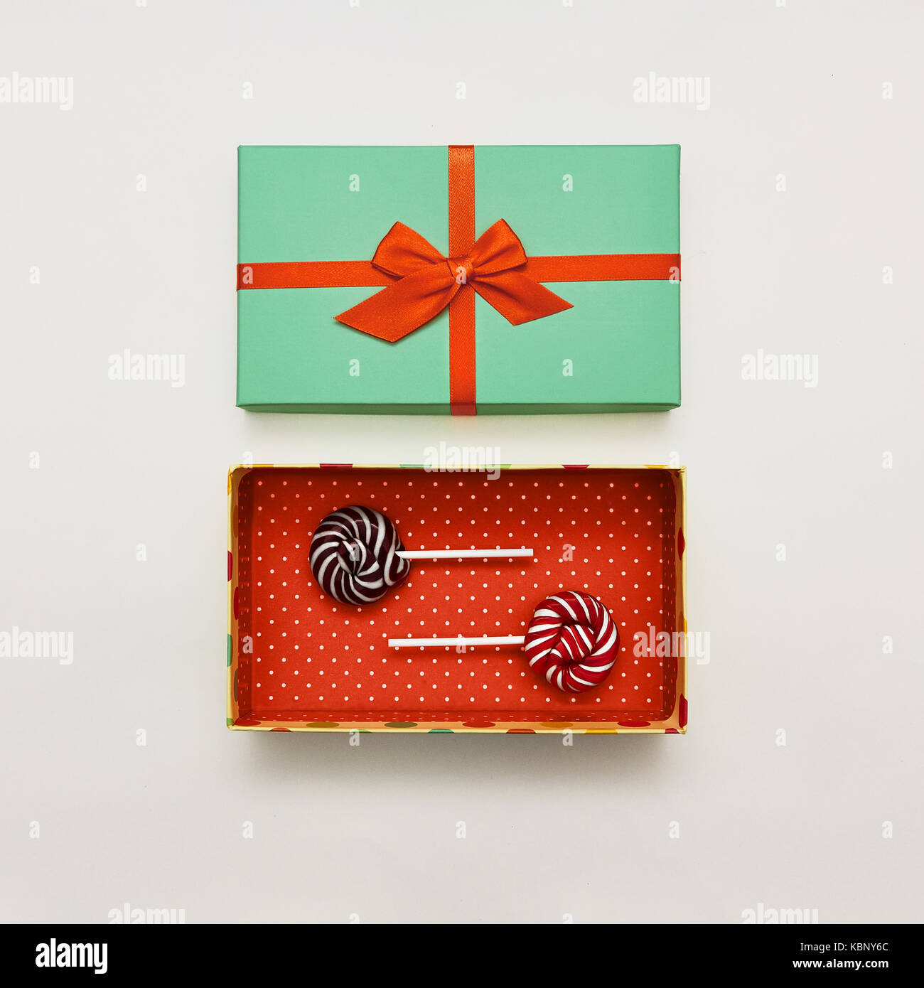 Lutscher flach mit weißem Hintergrund zwei farbigen Lutscher liegen in roter Geschenkbox mit Polka Dot Pattern Stockbild