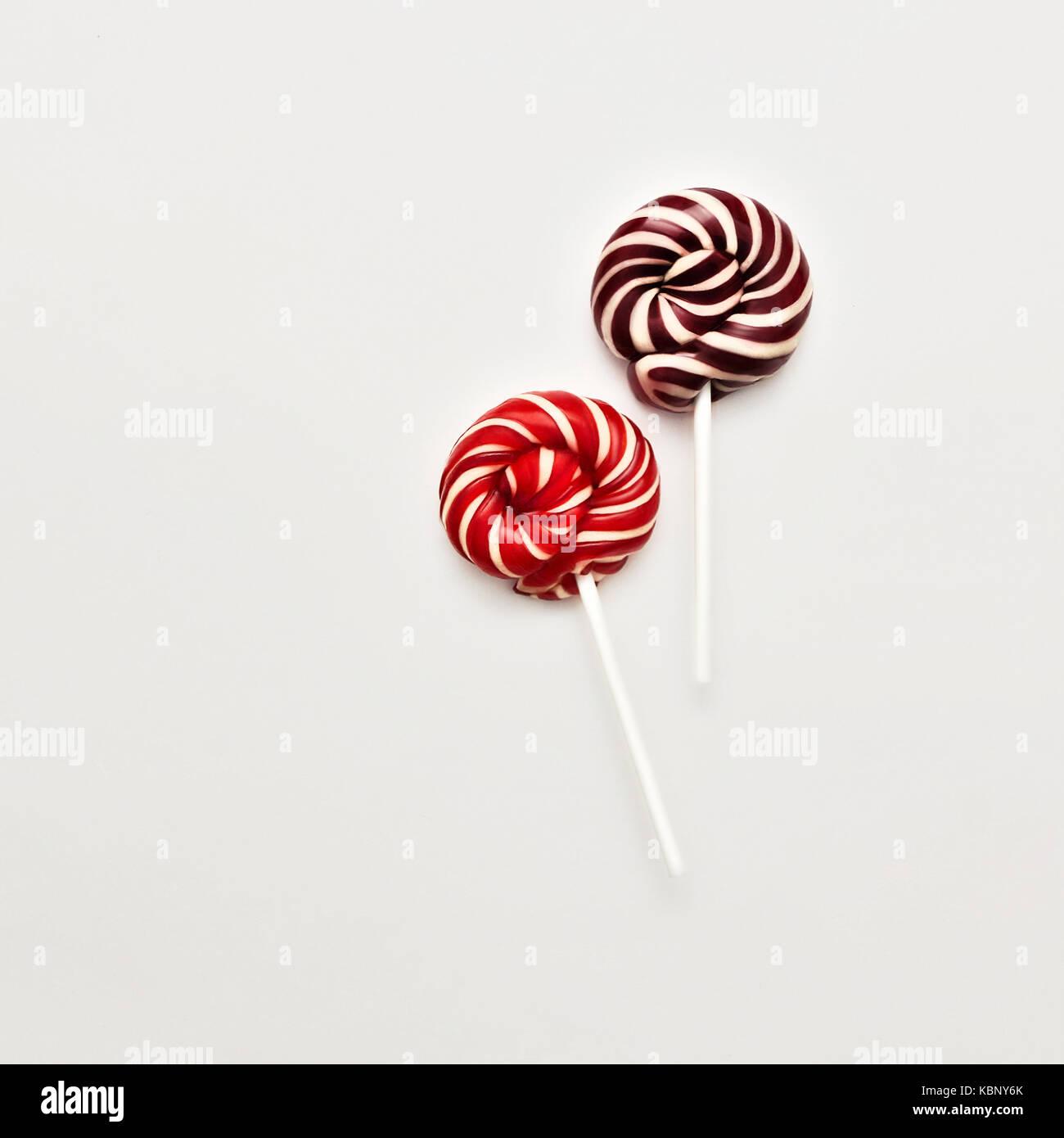 Lollipop flach minimalen Begriff zwei farbigen Lutscher liegen auf weißem Hintergrund klassische runde rot Stockbild