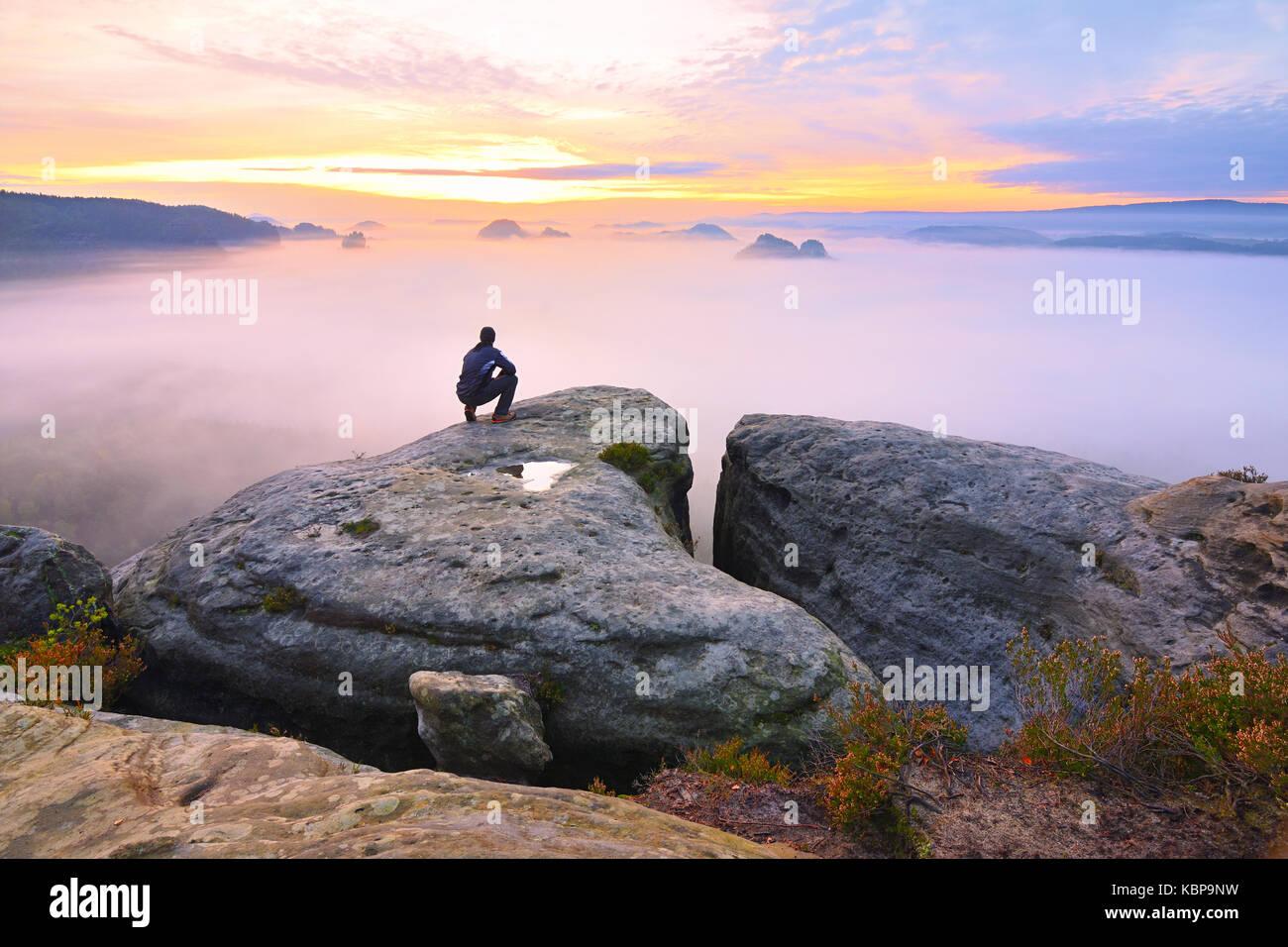 Scharfe hinten Mann Silhouette auf felsigen Gipfel. Wanderer befriedigen Aussicht genießen. Großer Mann Stockbild