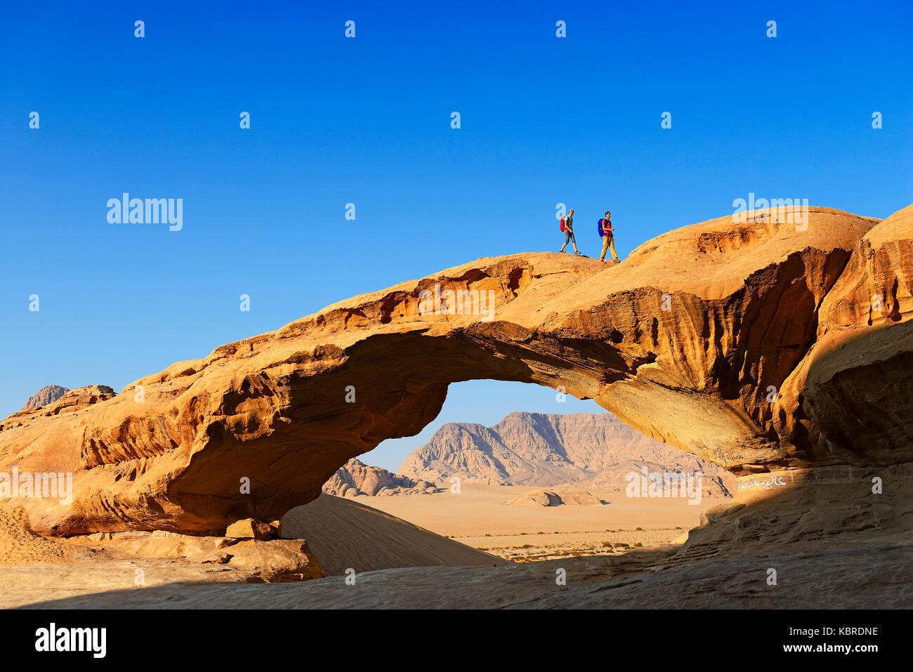 Paar Wandern am Rock-Arch namens Al Kharza, Wadi Rum, Jordanien Stockbild