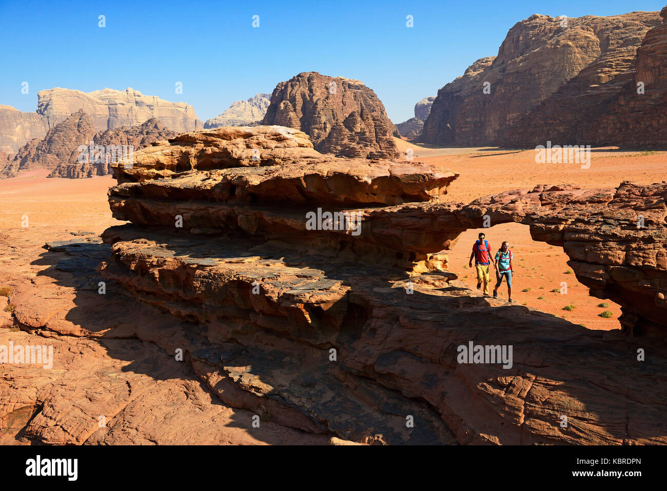 Paar Wandern am Rock Arch, Al Borg Alsagheer, Wadi Rum, Jordanien Stockbild