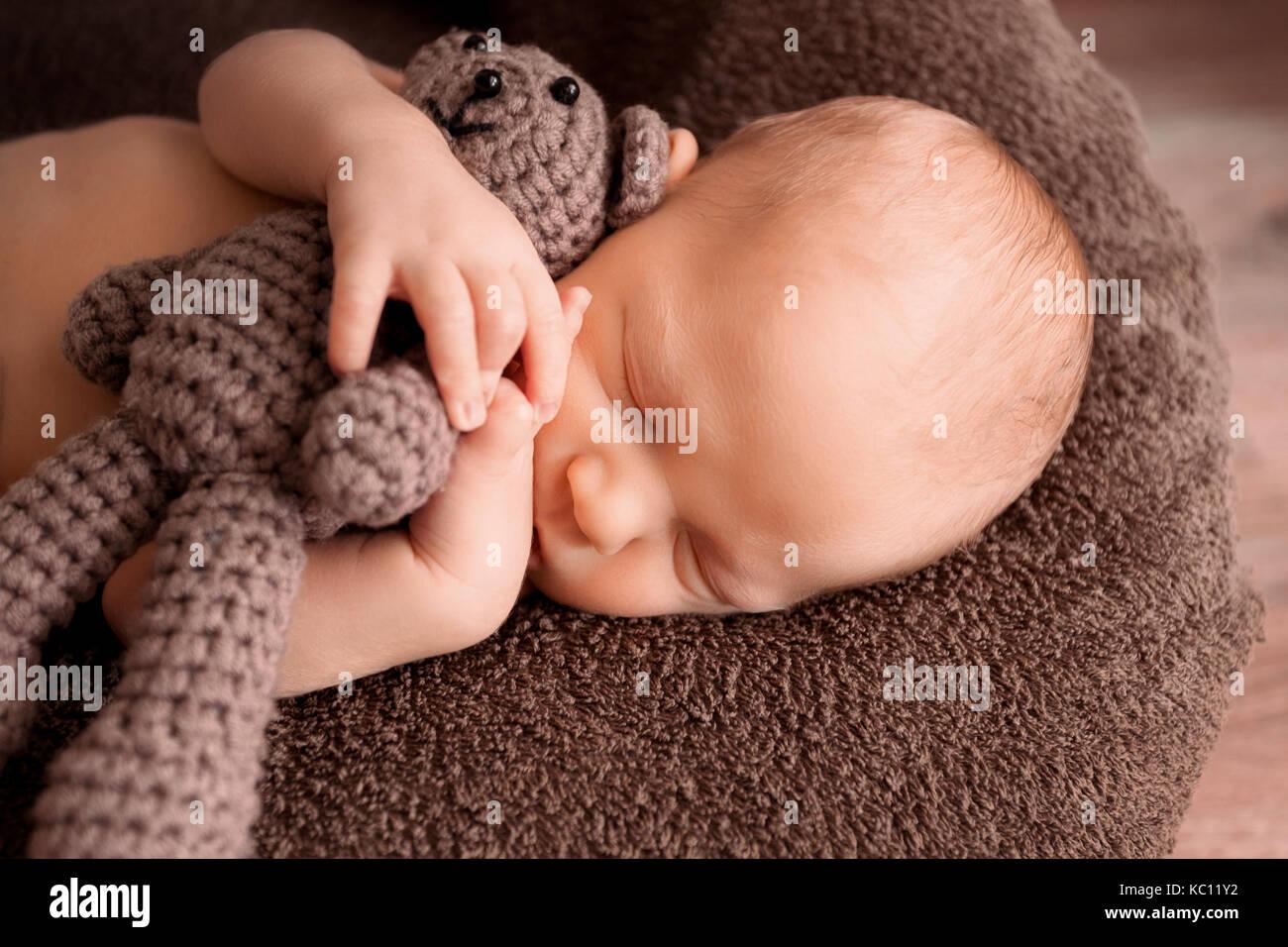 Neugeborene schlafen in einem schönen Stellen mit einem kleinen Bären Stockbild