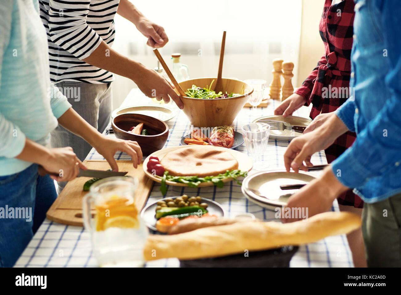 Im mittleren Abschnitt Gruppe junger Menschen die Vorbereitung Abendessen für festliche Feier am großen Stockbild