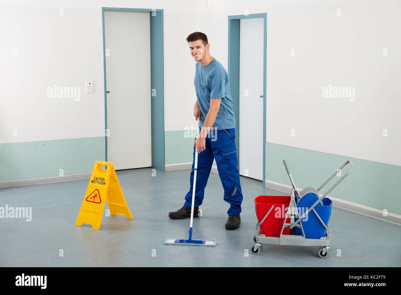 Fußboden Wischen ~ Junge männliche arbeiter mit der reinigung der geräte boden wischen
