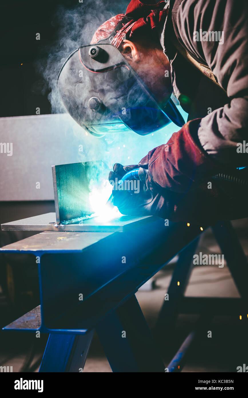 Industrielle Schweißer mit Taschenlampe und Schutzhelm in der grossen Halle schweißen Metallprofile Stockbild
