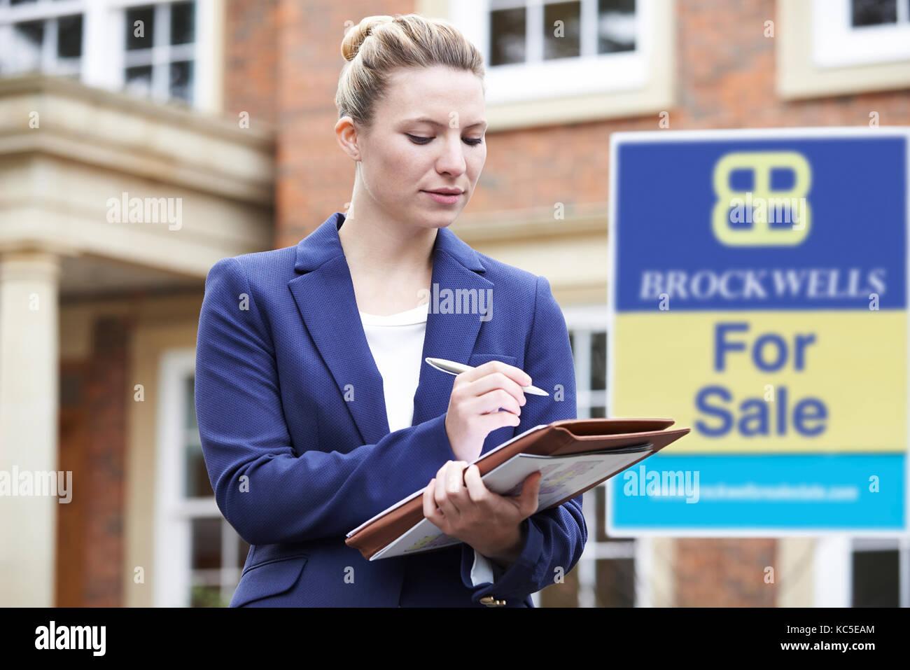 Weibliche Realtor außerhalb Wohnimmobilien mit für Verkauf Zeichen Stockbild