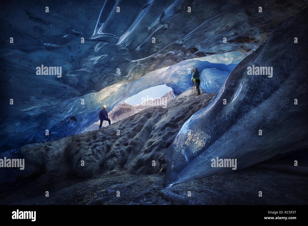 Explorers Paar in einer Eishöhle während einer Fotografie Expedition im Athabasca Gletscher Stockbild