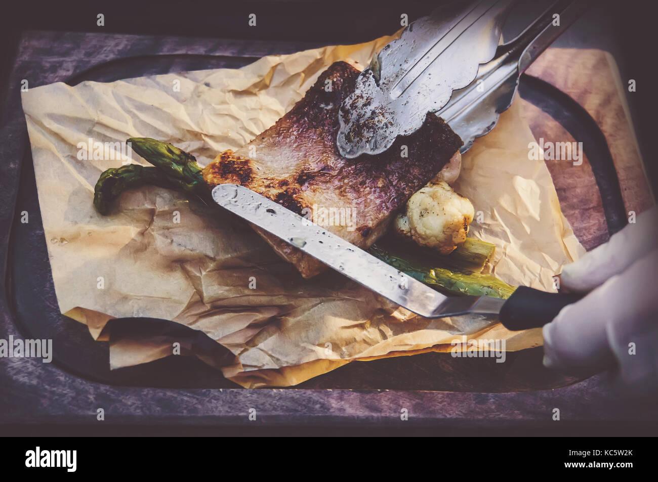 Prozess der Küche Fisch. Hände Köche in saubere, weiße Handschuhe setzt gegrillten Fisch auf Stockbild