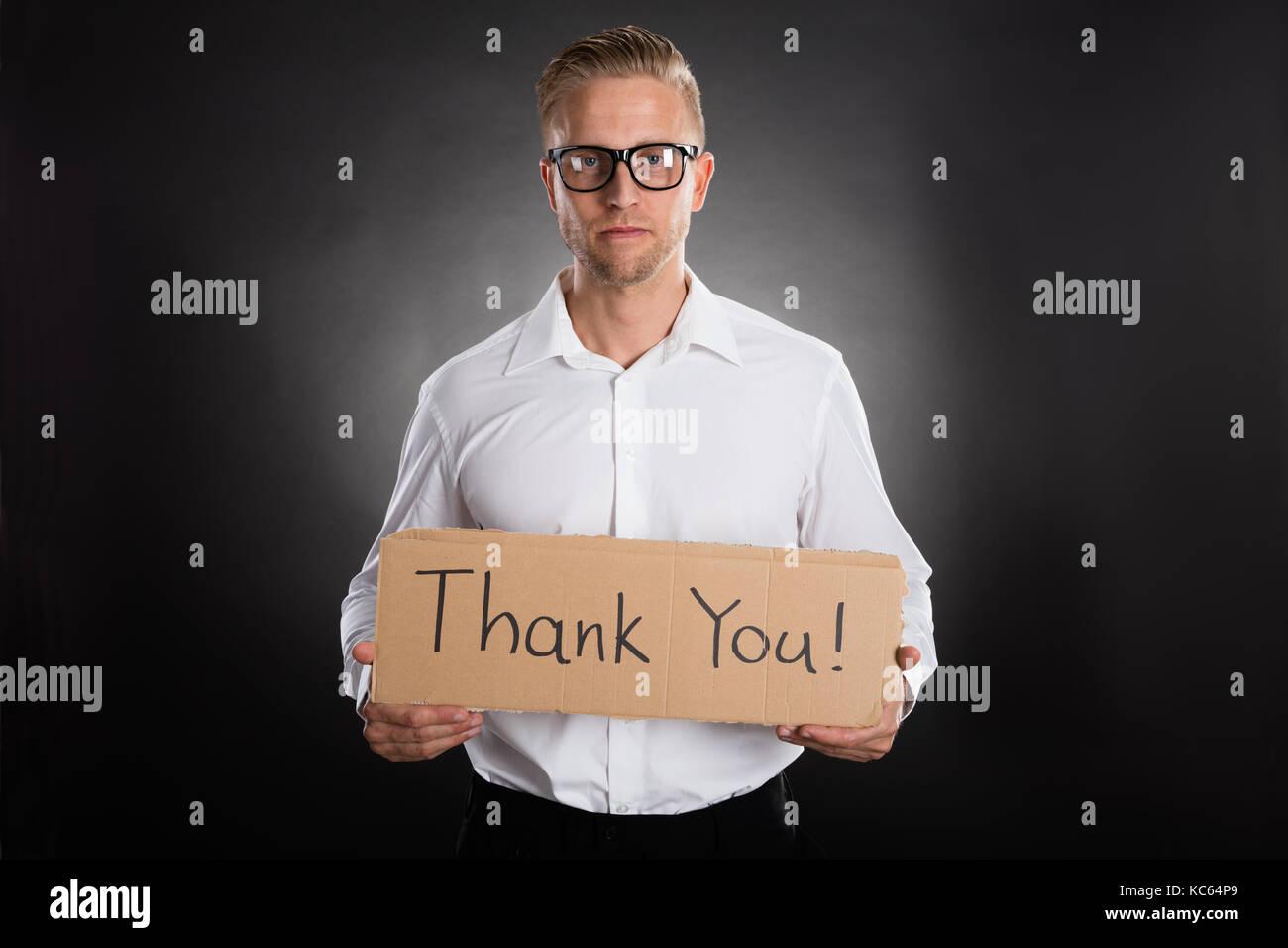 Mann, Karton mit vielen Dank Text Darauf auf schwarzem Hintergrund geschrieben Stockbild
