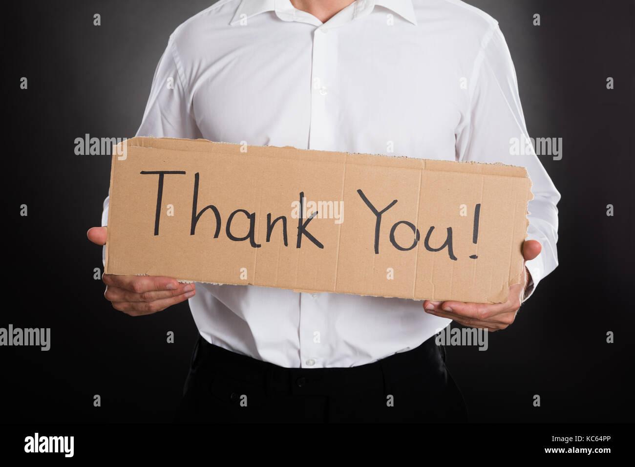 Nahaufnahme der Mann mit Pappe mit vielen Dank Text auf schwarzem Hintergrund Stockbild