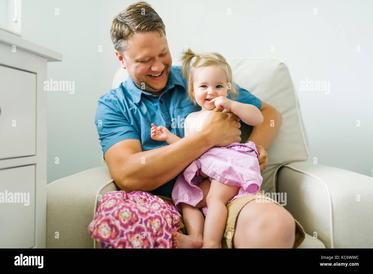 Vater mit baby girl (12-17 Monate) im Wohnzimmer sitzen Stockbild
