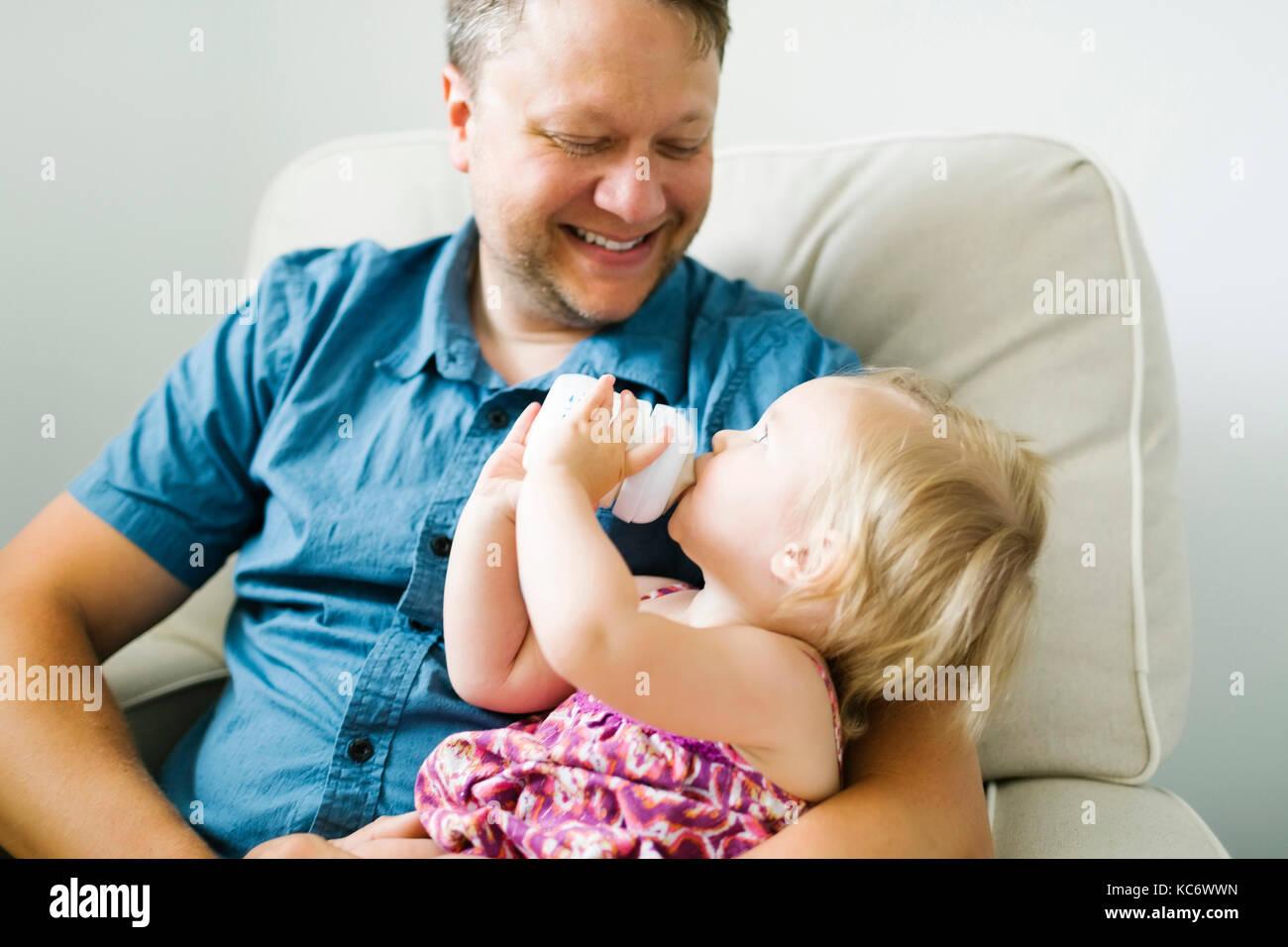 Vater feeding baby girl (12-17 Monate) im Wohnzimmer. Stockbild