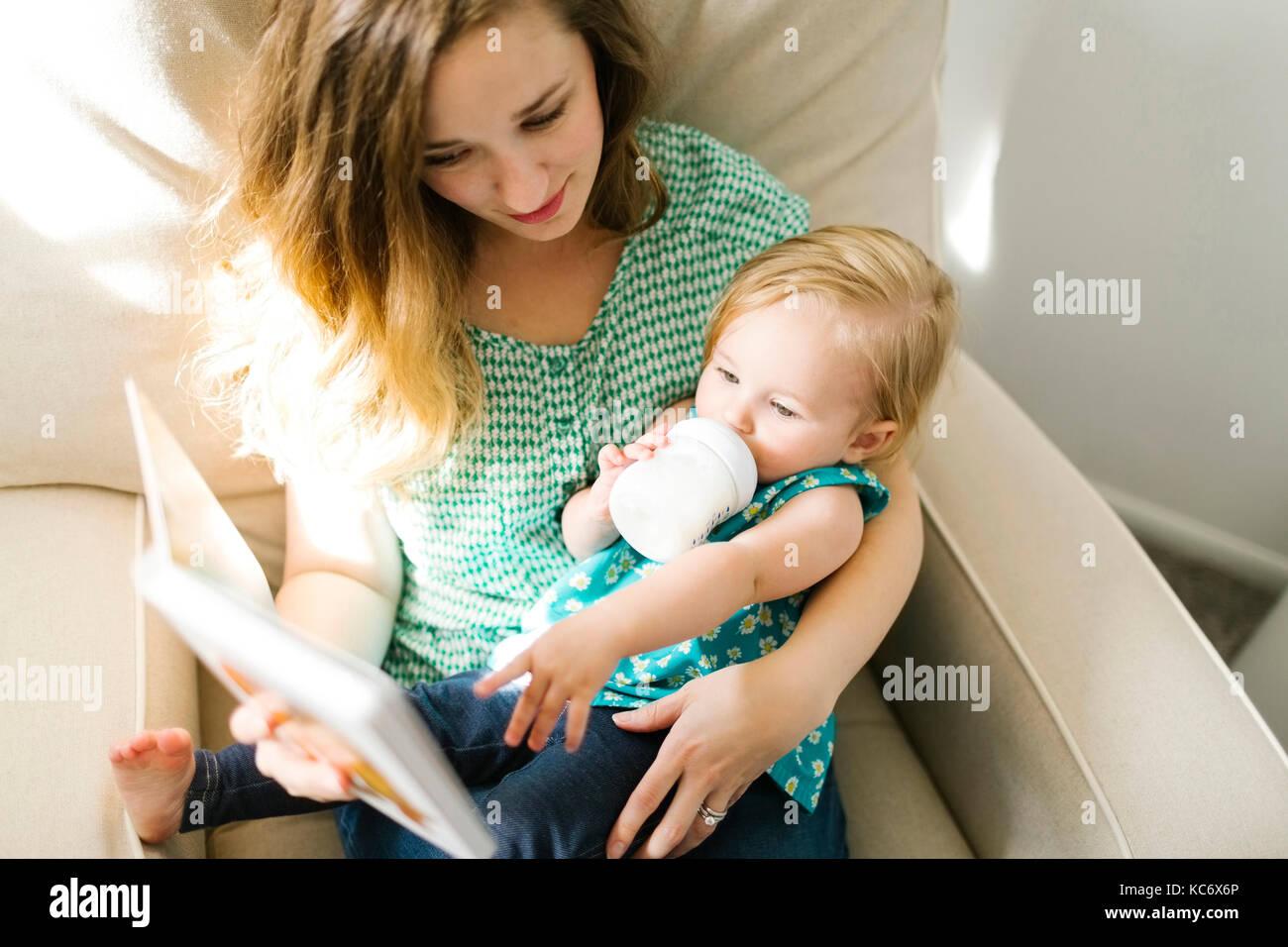 Mutter mit Baby girl (12-17 Monate) in Wohnzimmer und lesen Buch sitzen Stockbild