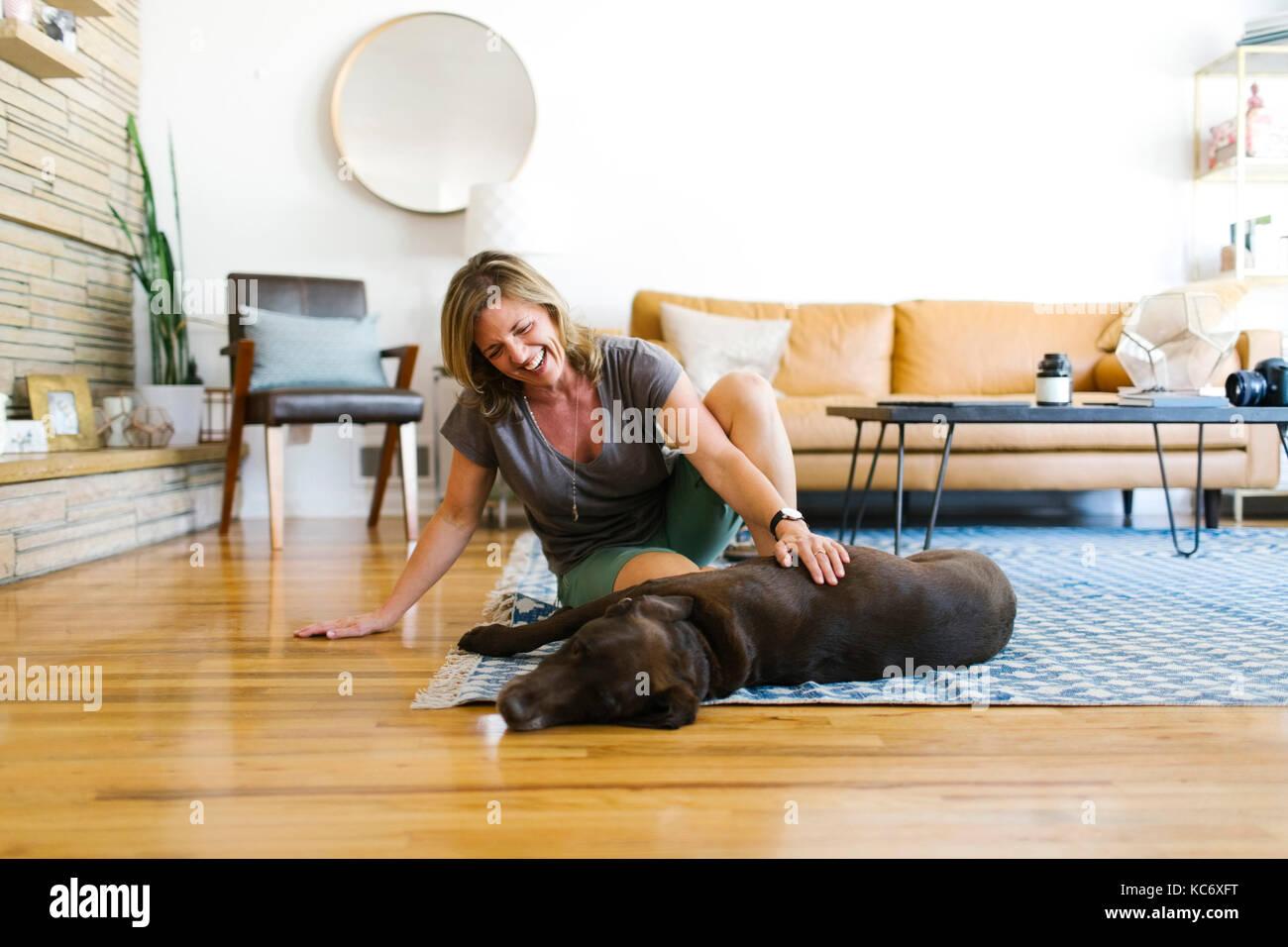 Frau streicheln Labrador Retriever im Wohnzimmer Stockbild