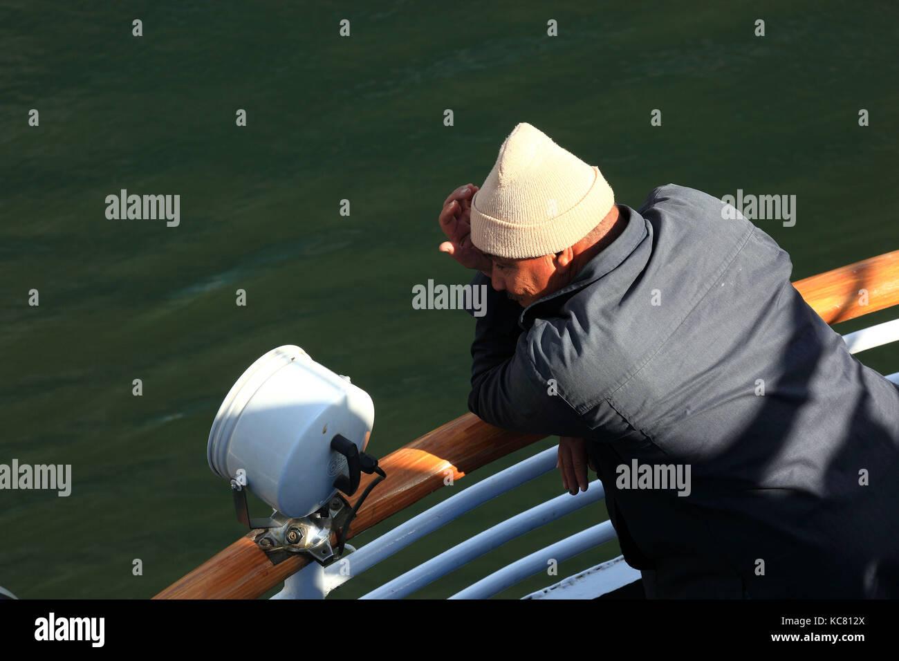 Man steht an der Reling eines Schiffes Stockbild