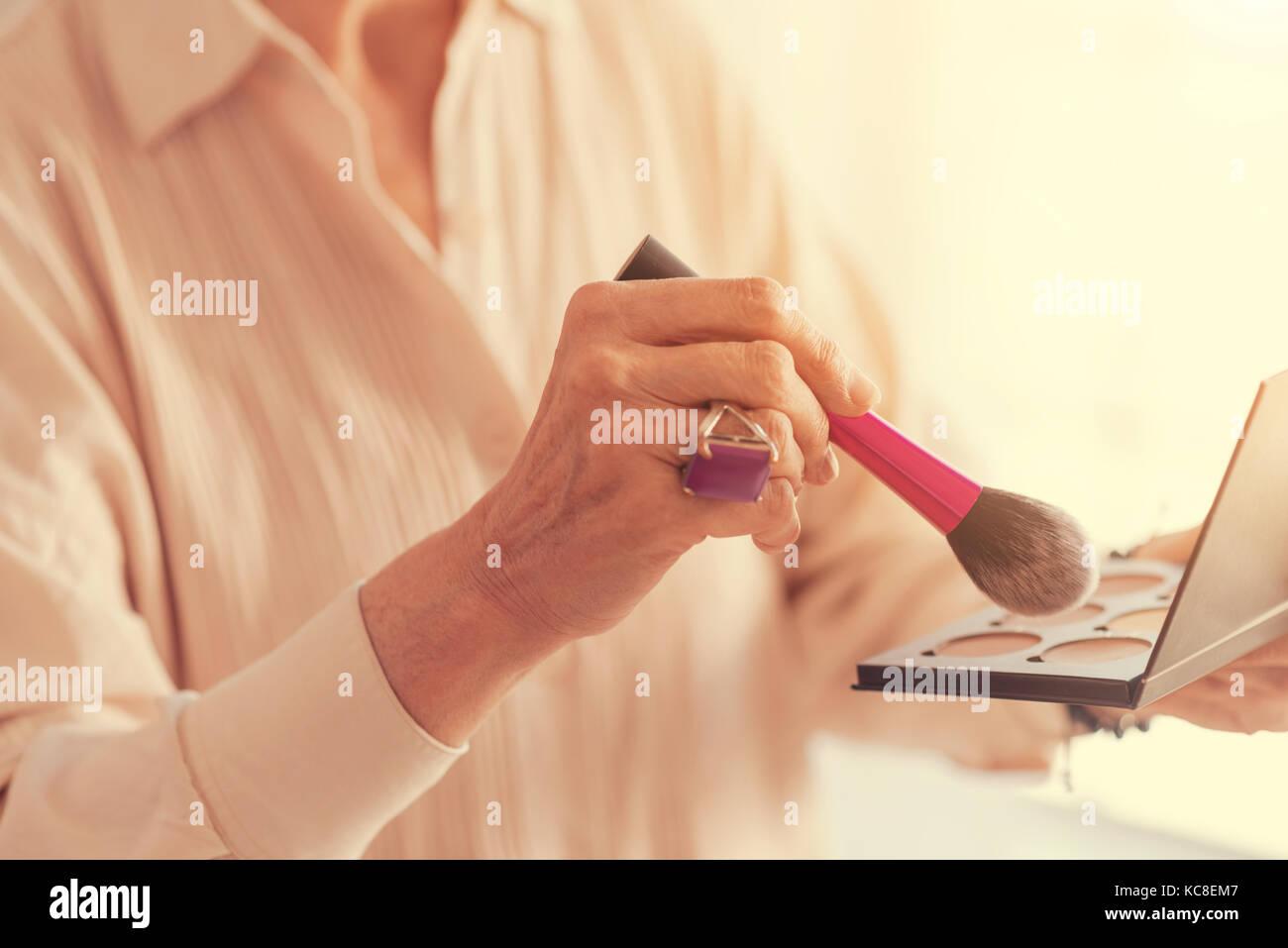 Nahaufnahme der Powder Brush in Händen eines schön gealterte Frau Stockbild