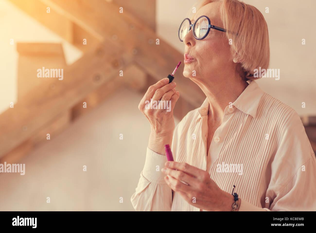 Schön gealterte Frau Anwendung Lip Gloss Stockbild