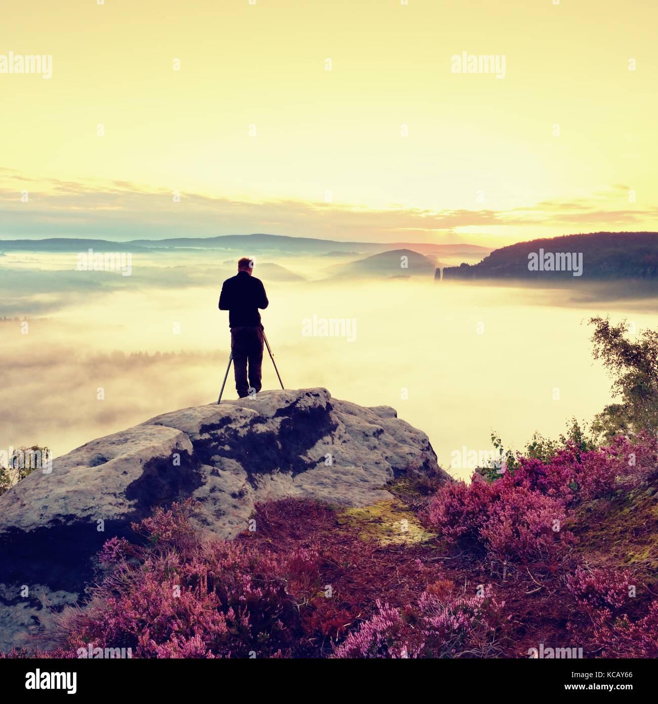 Professioneller Fotograf nimmt Fotos mit Kamera und Stativ auf der Spitze des Felsens. verträumte fogy Landschaft, Stockbild