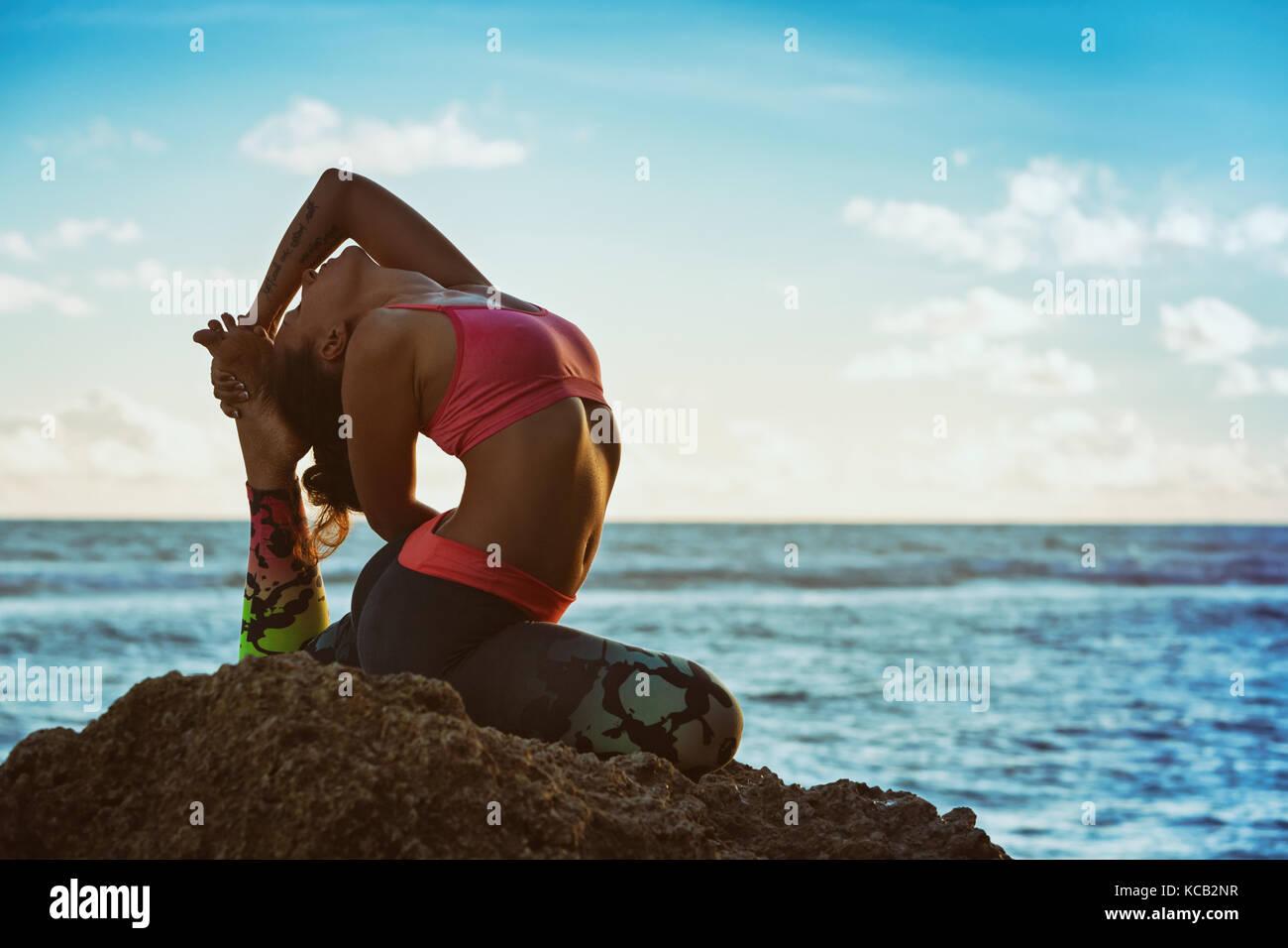 Meditation über Sonnenuntergang Himmel Hintergrund. Junge aktive Frau sitzen in Yoga pose am Strand Felsen, Stockbild