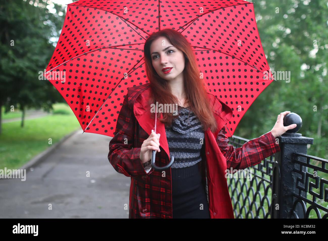 Frau in eine Regenjacke und einen Regenschirm Stockbild