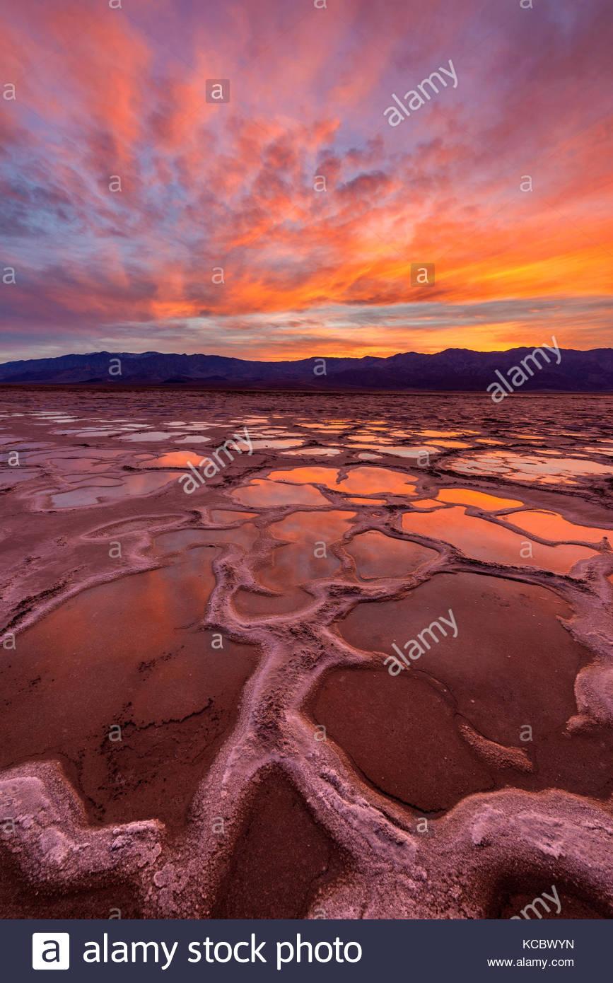 Playa nach dem Regen als Sonne über die Panamint Range, Death Valley National Park, Kalifornien Stockbild