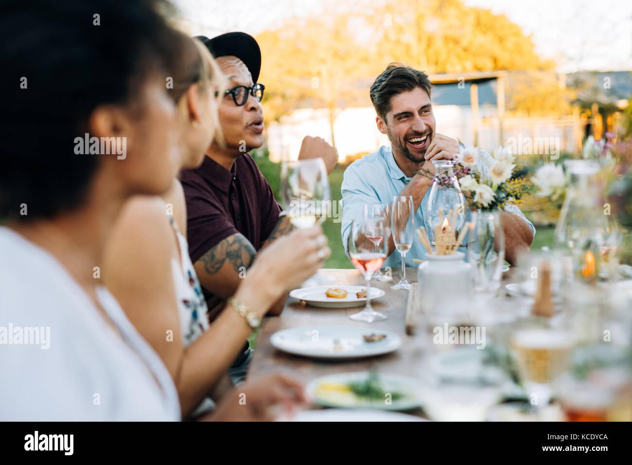 Junger Mann Lachen beim Sitzen mit Freunden im Freien. Freunde genießen Sommer Mahlzeiten im Restaurant im Freien. Stockfoto