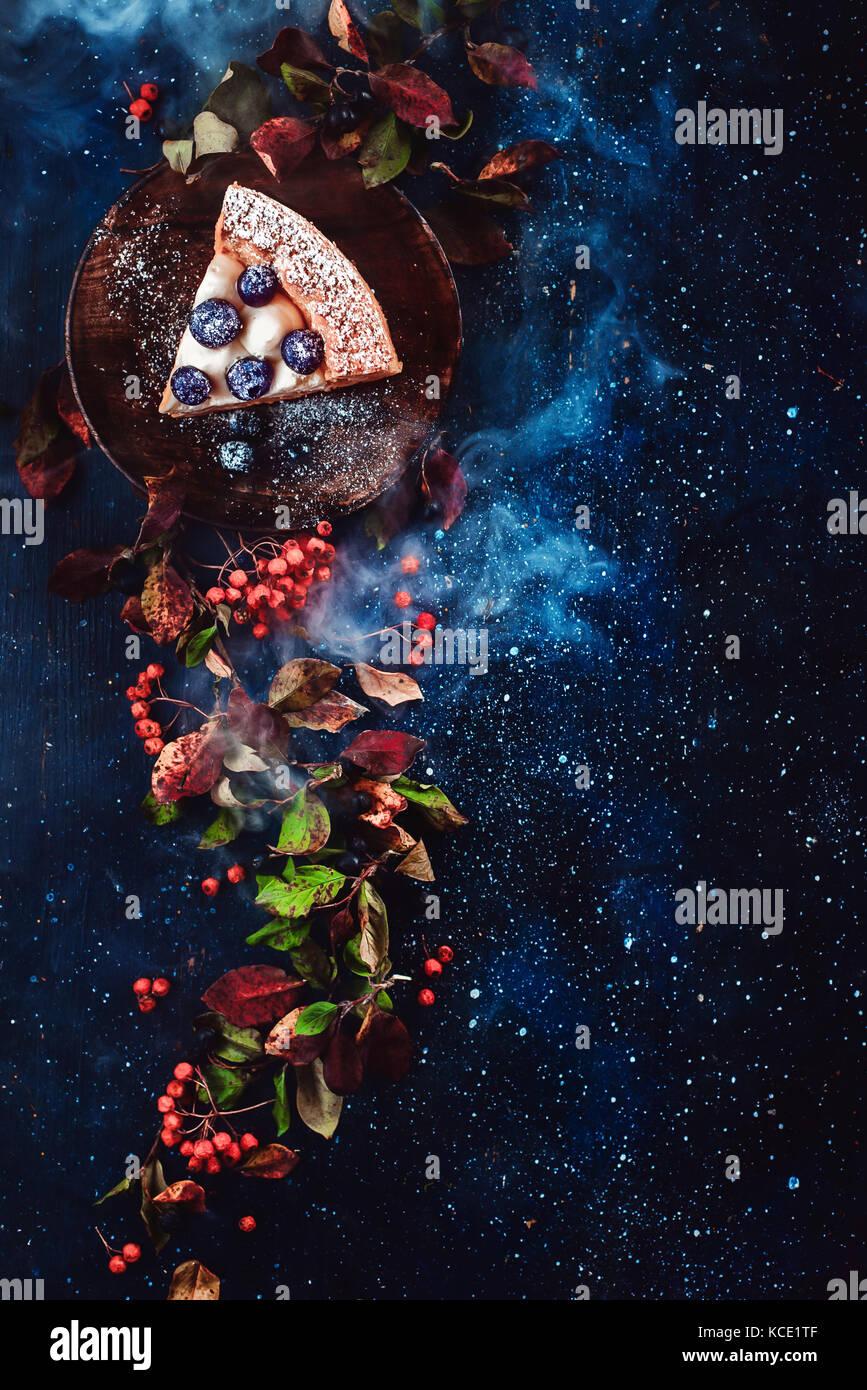 Florale mit einem Stück Heidelbeerkuchen, Herbst Blätter, Beeren und blauer Rauch auf einem dunklen Hintergrund. Stockbild