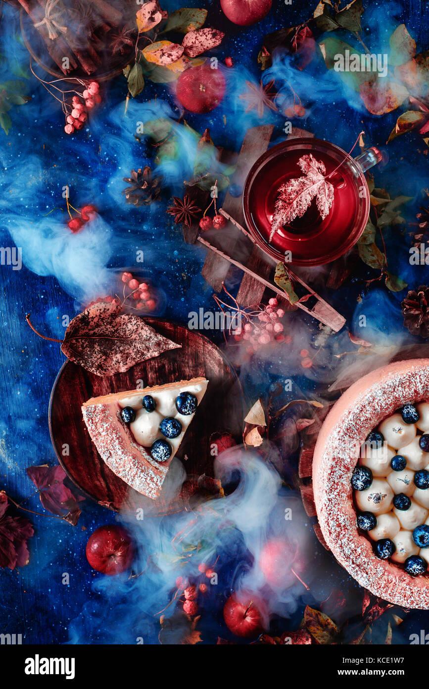 Dunkle Herbst Stilleben mit Schlagsahne Blaubeere Kuchen, heißen Tee und Blumenschmuck auf einem Hintergrund mit Stockfoto
