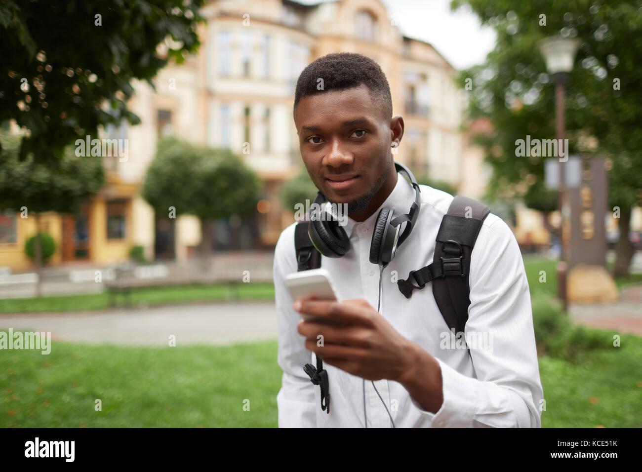 Afrikanischen Studenten chatten, schreiben Nachricht mit Smart Phone. Stockbild