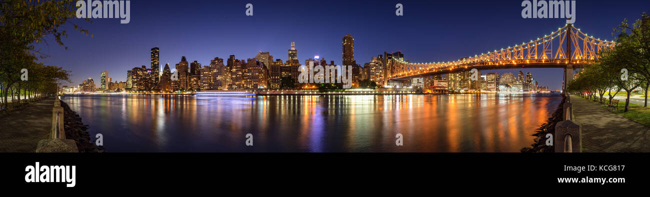 Panoramablick am Abend Blick auf Manhattan Midtown East von Roosevelt Island mit der beleuchteten die Queensboro Bridge. New York City Stockfoto