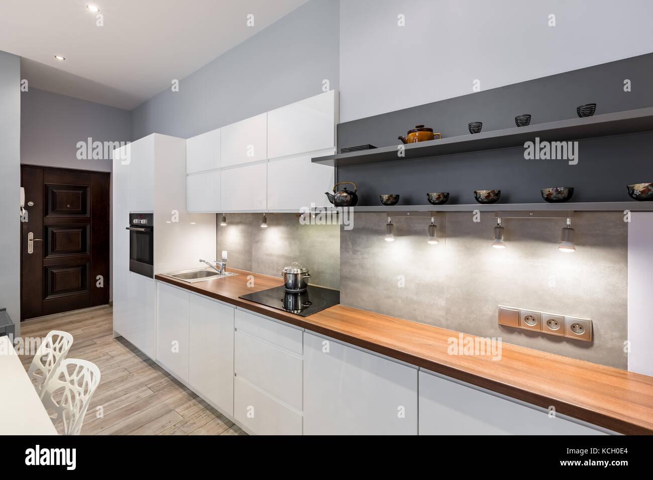 Moderne, weiße Küche mit Holz- Arbeitsplatte und LED-Beleuchtung ...
