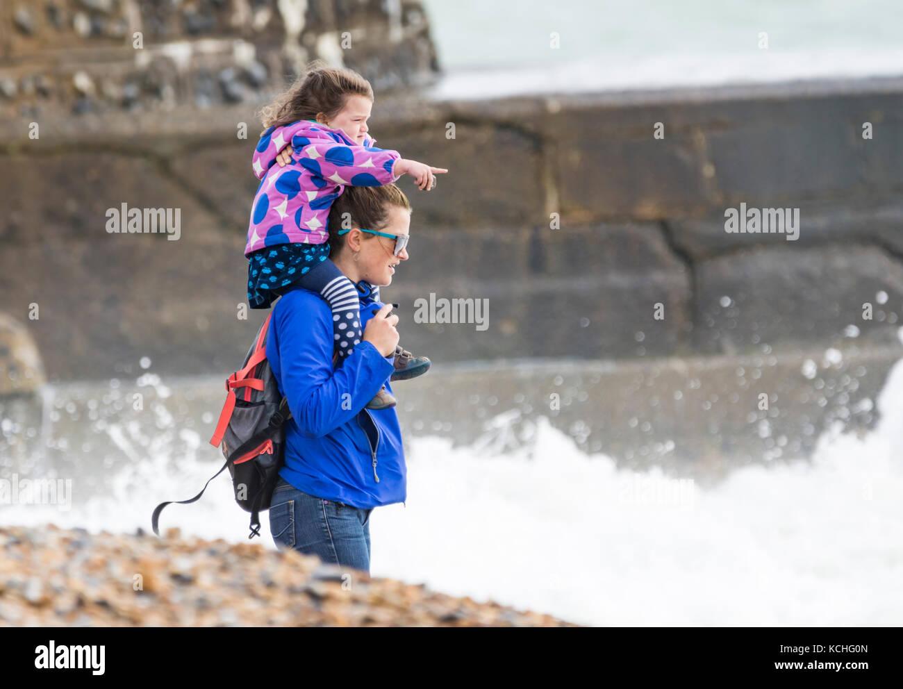 Junge Mädchen, Frau, Schultern (piggyback Ride) auf einem Strand in armen windigen Wetter im Herbst durchgeführt, Stockbild