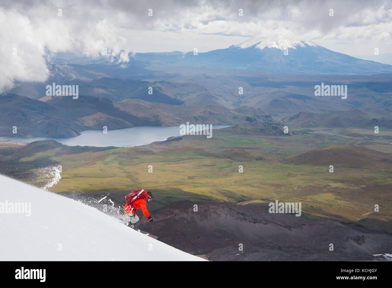 Eine männliche Skifahrer auf einem Abstieg über den Hängen des Vulkan Antisana mit cotopaxi hinter, Stockbild