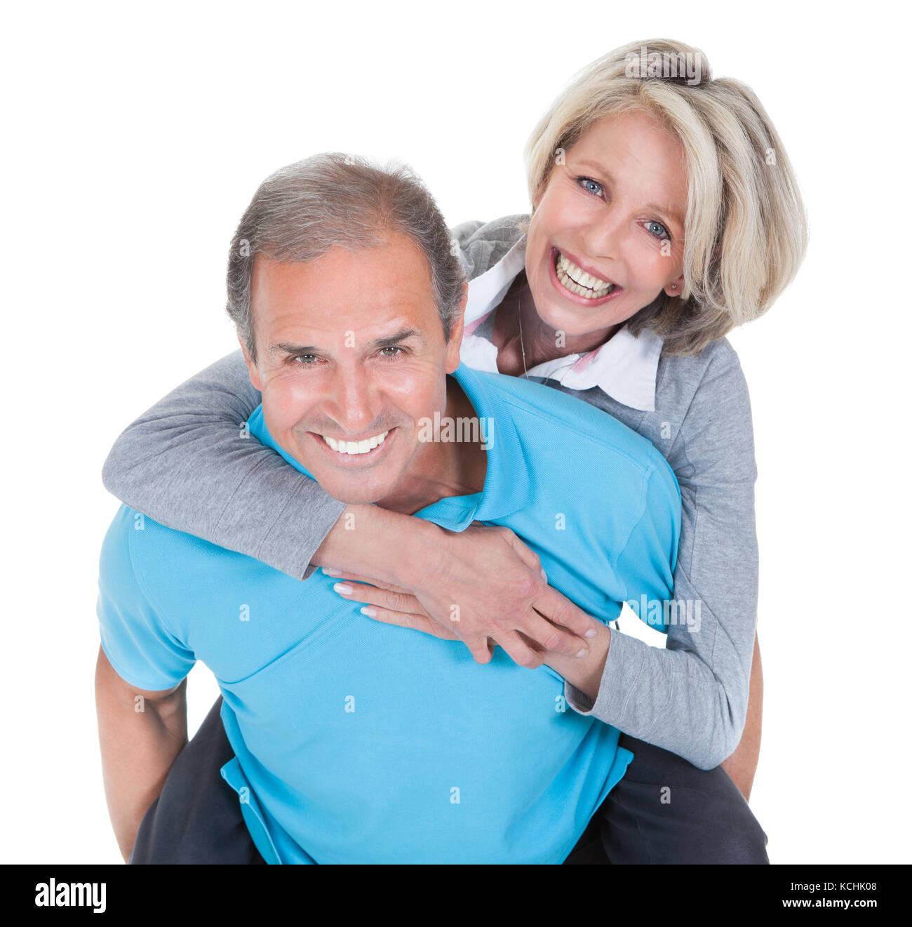 Reifer Mann seine glückliche Ehefrau auf weißem Hintergrund Netzwerk zugreift. Stockbild