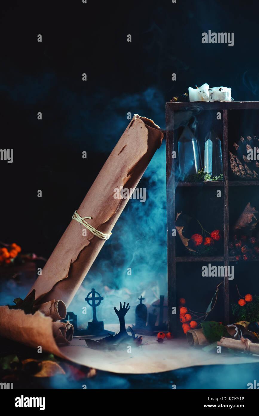 Friedhof mit steigenden Zombies Silhouetten in konzeptionellen Halloween Stillleben mit Rauch, wirards Arbeitsplatz, Stockbild