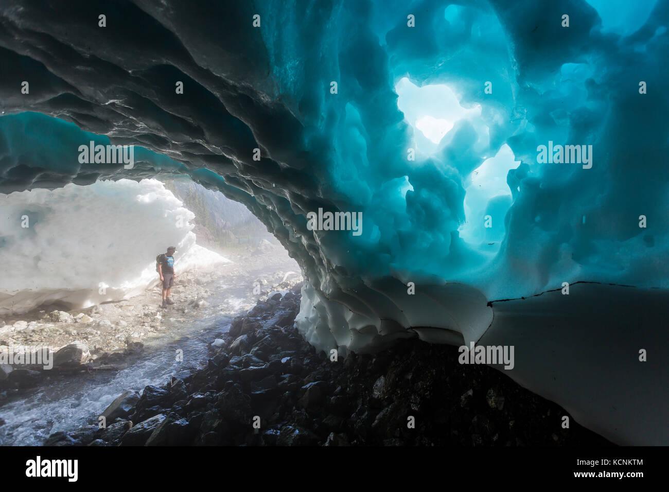Ein Wanderer geht durch eine schneehöhle am Sockel des Jahrhunderts sam See, Strathcona Park, Vancouver Island, Stockbild